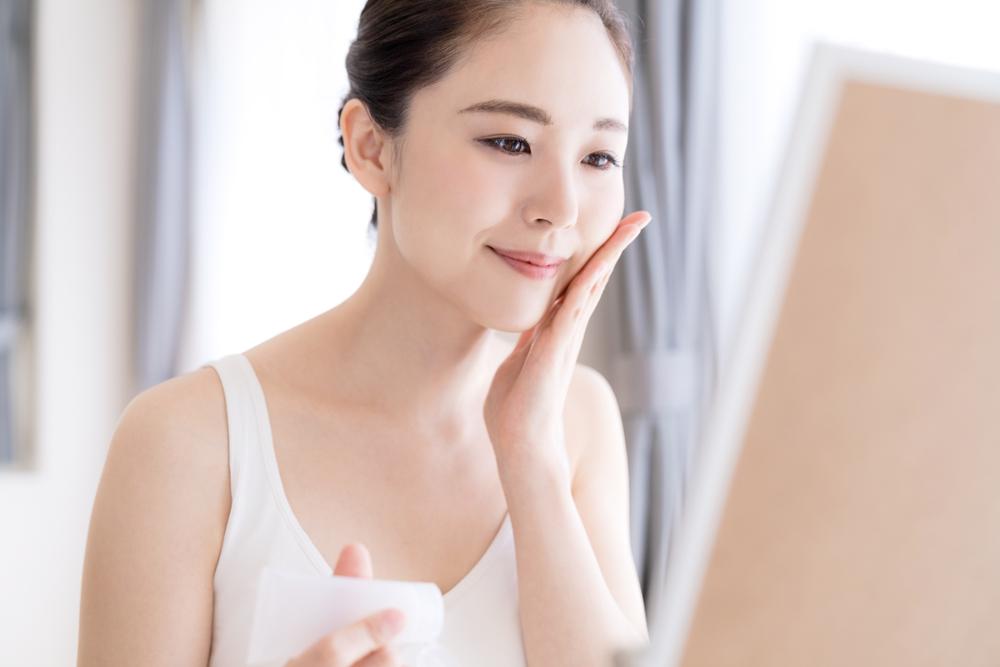肌の状態を確認しながらスキンケアする女性