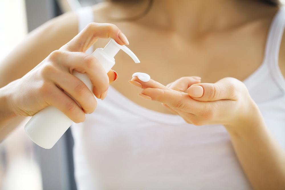 スキンケアアイテムを手に取る女性の手元