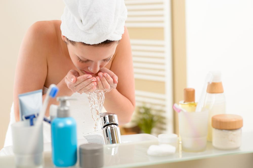 水で顔を洗っている人
