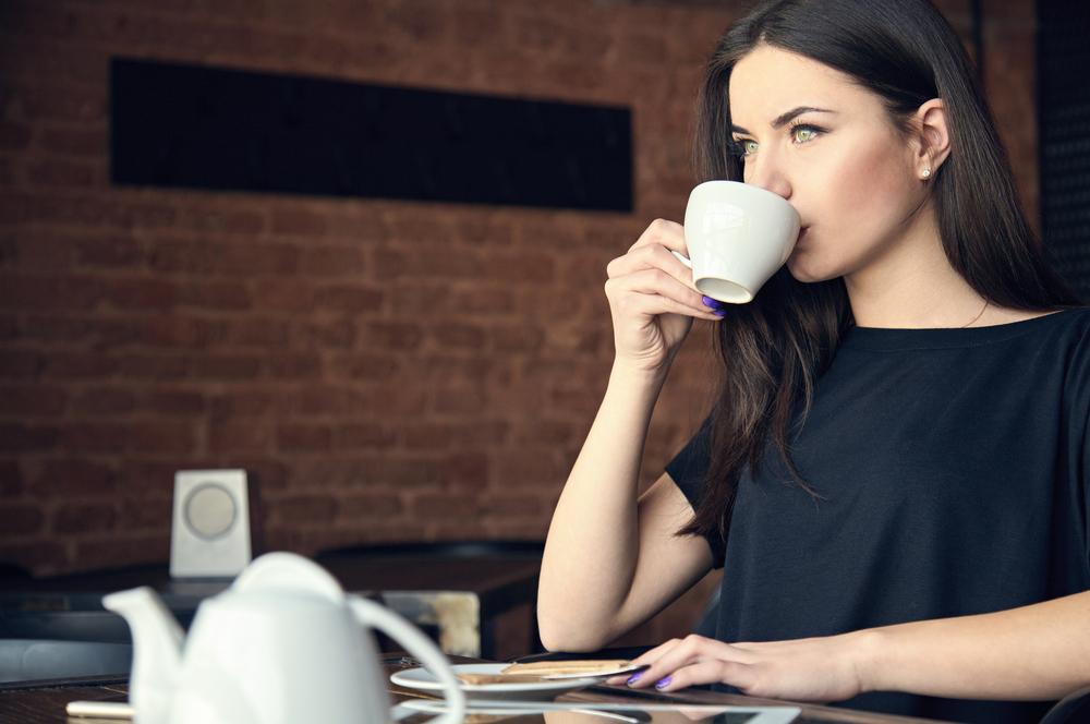 マナーを守ってコーヒーを飲んでいる女性