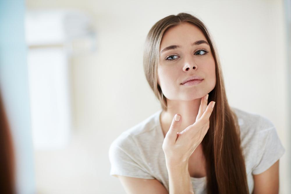 鏡で肌チェックをする女性
