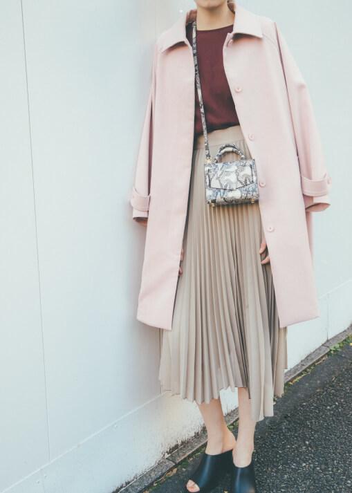ピンクのステンカラーコート×ベージュのプリーツスカートのコーデ
