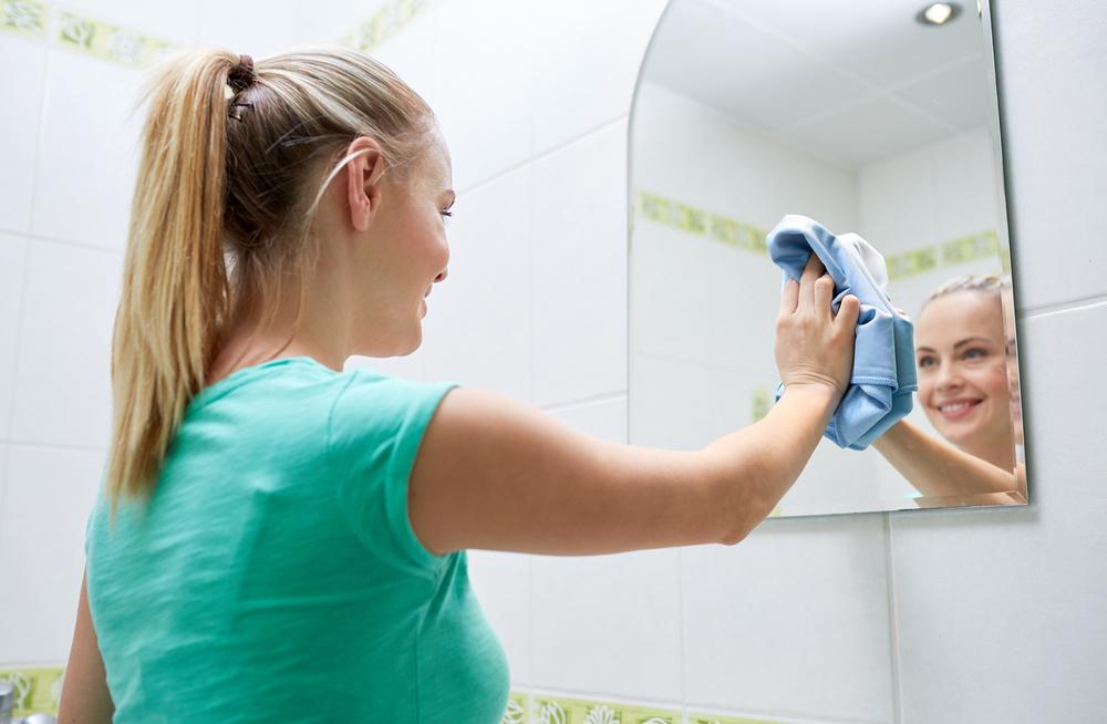 鏡の掃除をしている女性