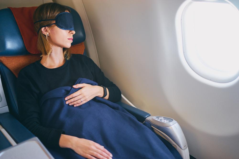飛行機で寝る女性