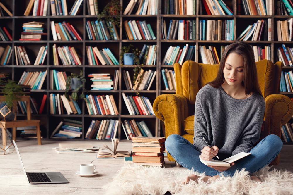 本棚とメモを書く女性