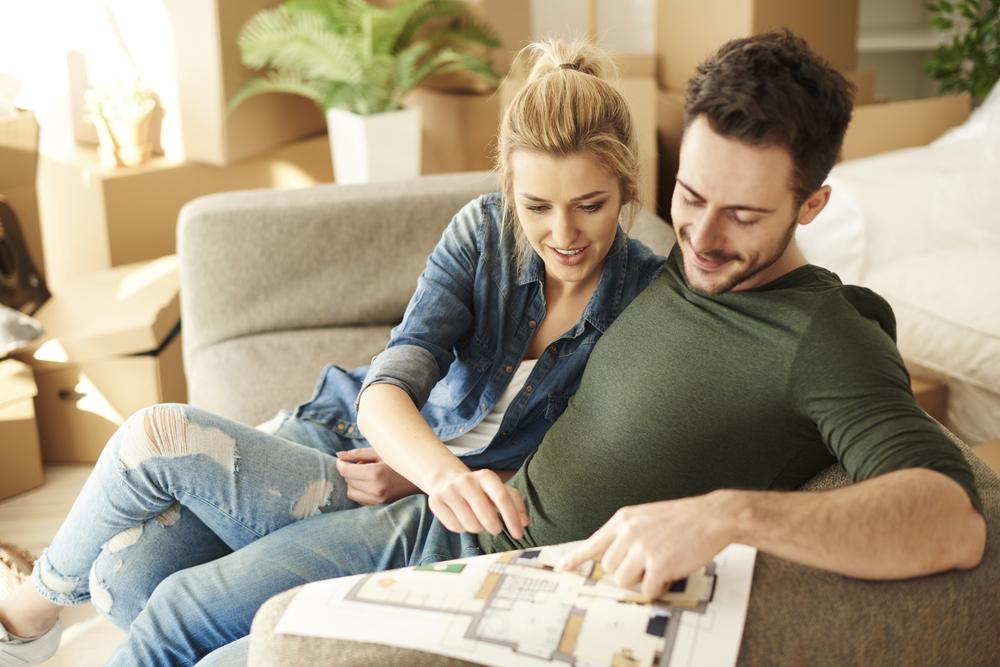 結婚後の新居で間取りの相談をしているカップル