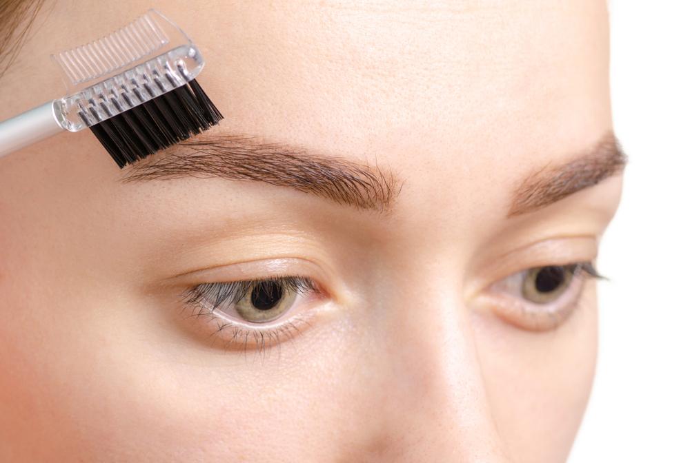 眉毛をブラシで整えている女性