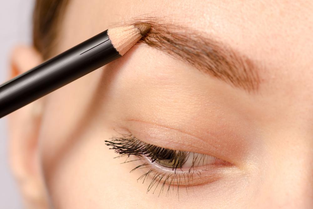 眉毛をペンシルで描いている女性