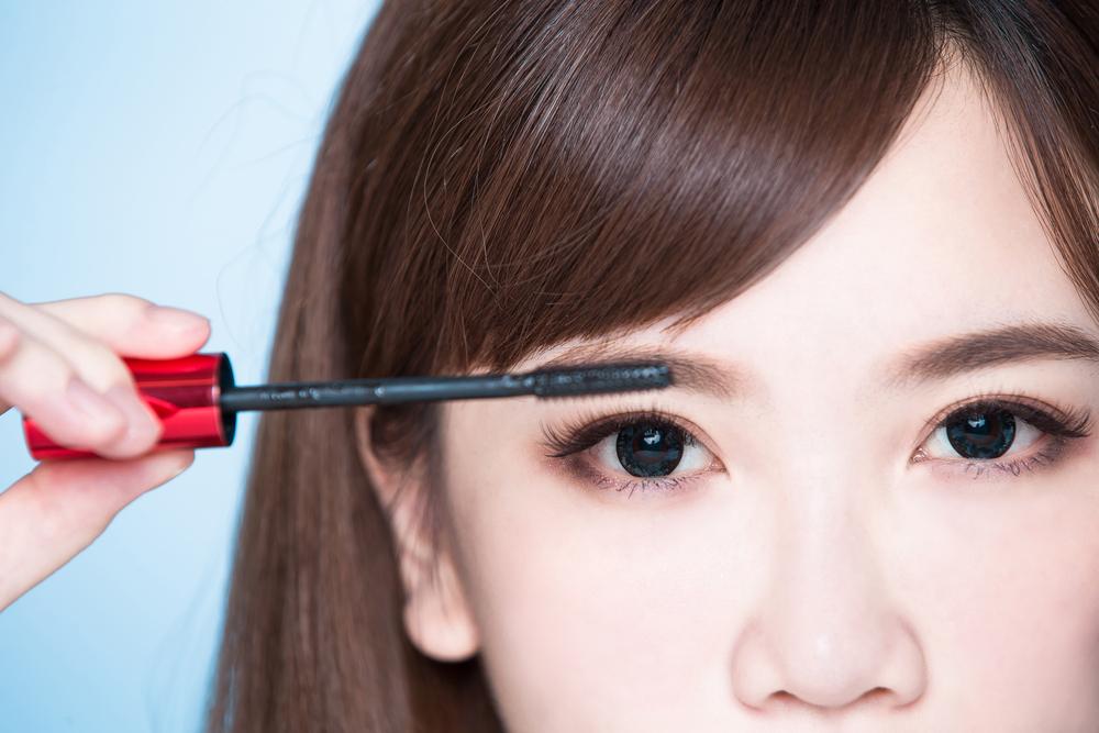 眉毛を描いている女性