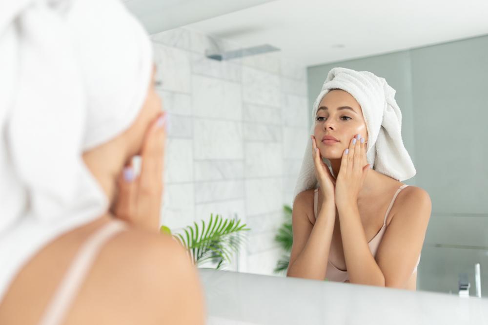 鏡で頬をチェックする女性