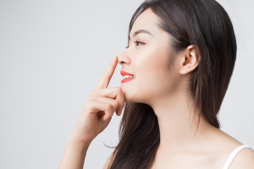 鼻を触る女性