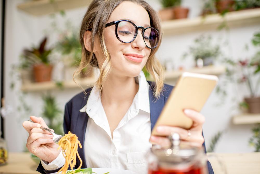 食事中に左手でスマホを持っているマナーの悪い女性