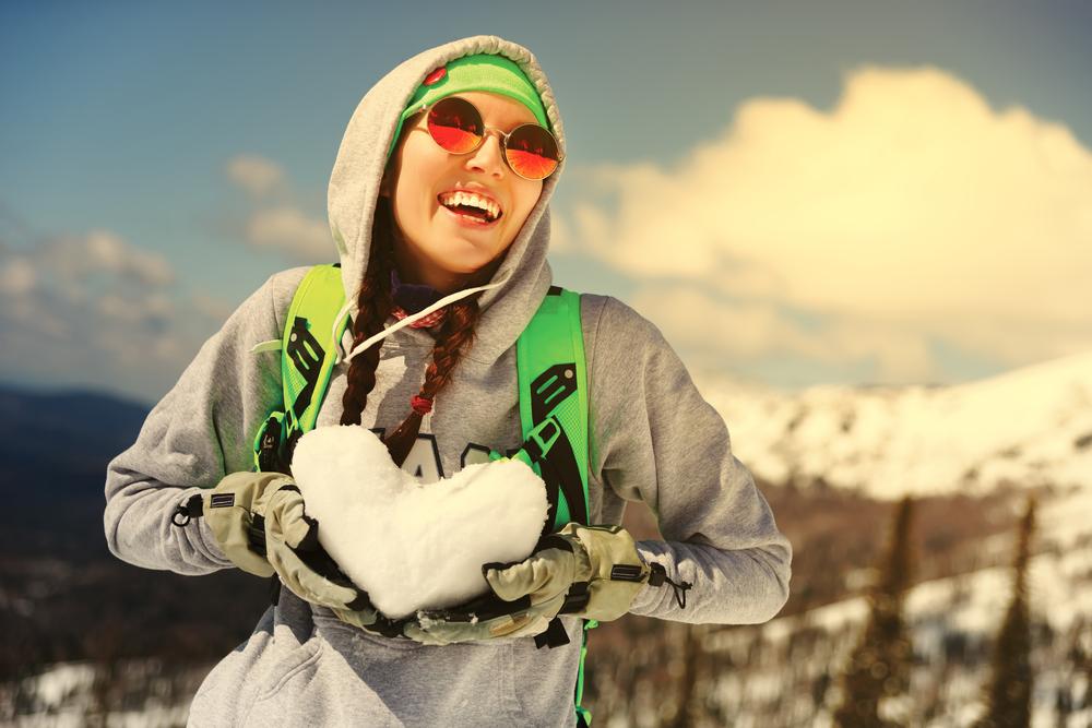 雪でハートを作る女性