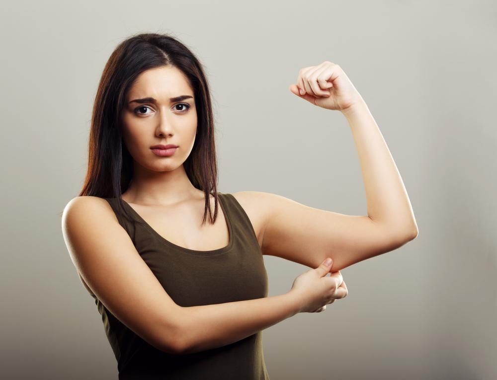 二の腕の肉をつかむ女性