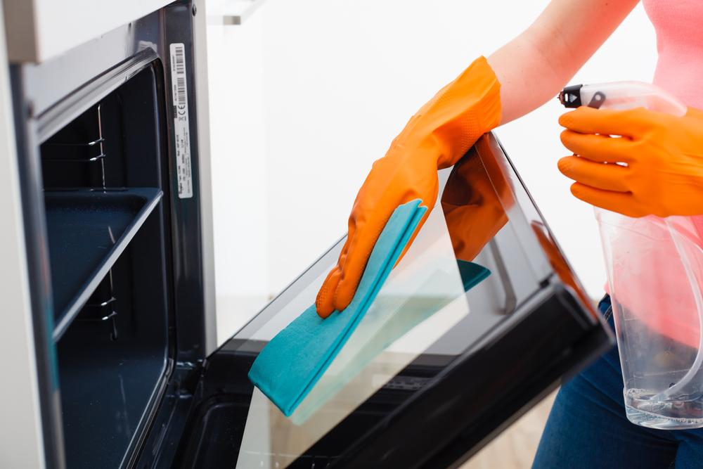 キッチンのオーブンを掃除している女性