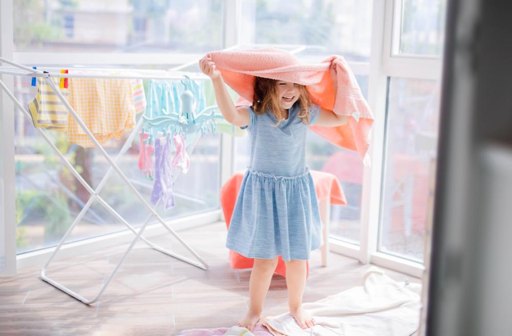 部屋干しした洗濯物の近くで遊ぶ女の子
