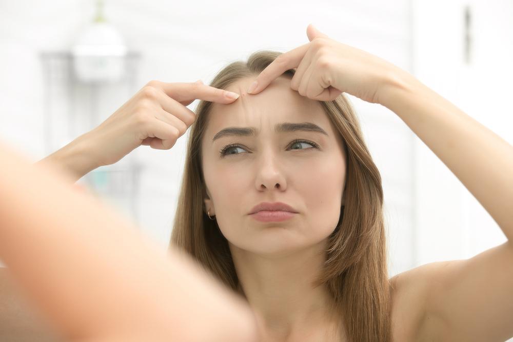 鏡でニキビを確認する女性