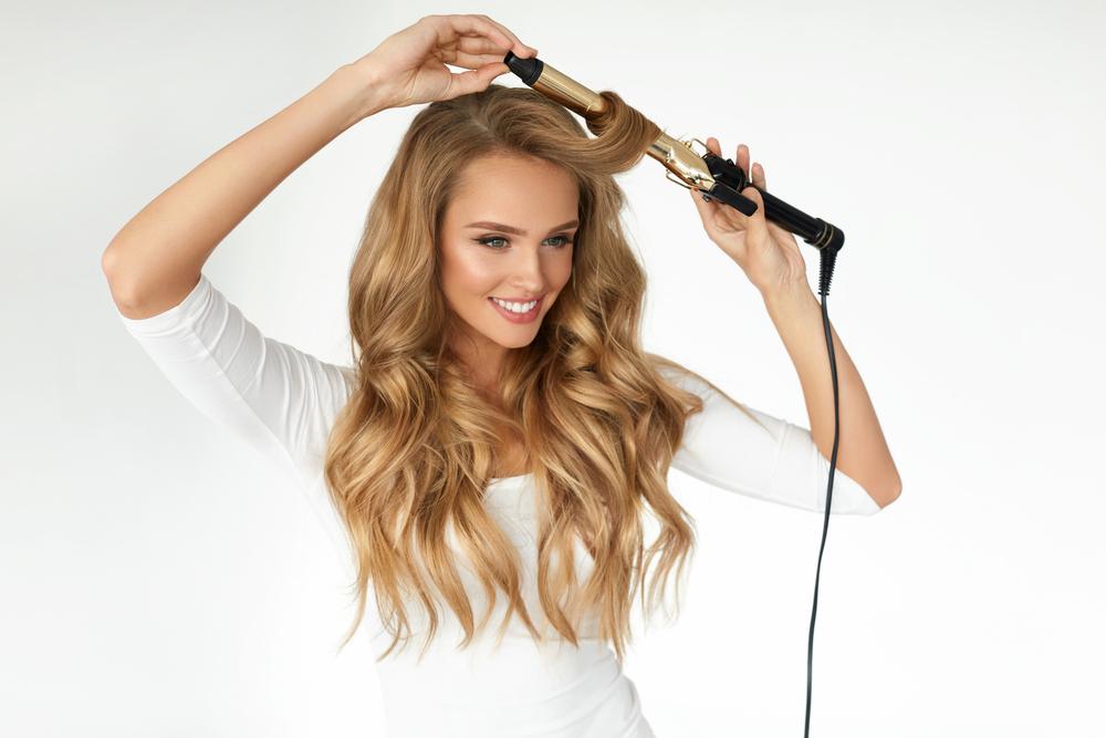 コテで前髪を流すセットをしている女性