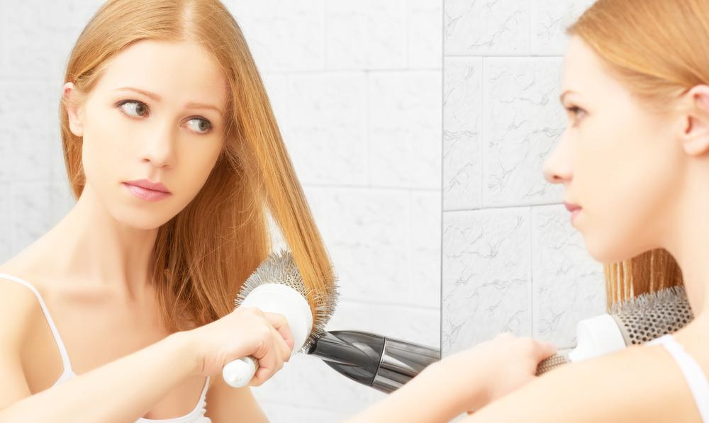 ドライヤーで前髪を流すセットをしている女性