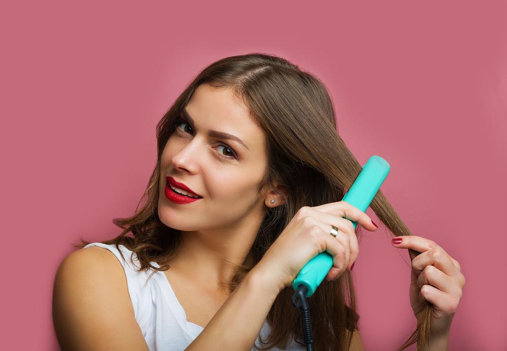 アイロンで前髪を流すセットをしている女性