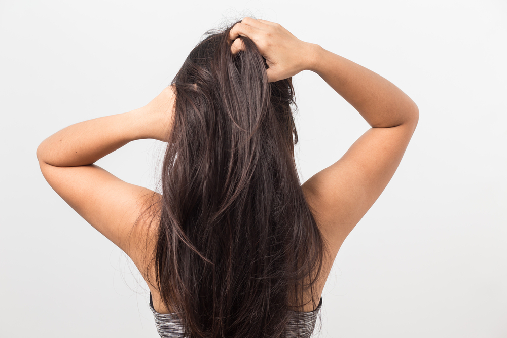 髪をかきあげている女性の後ろ姿