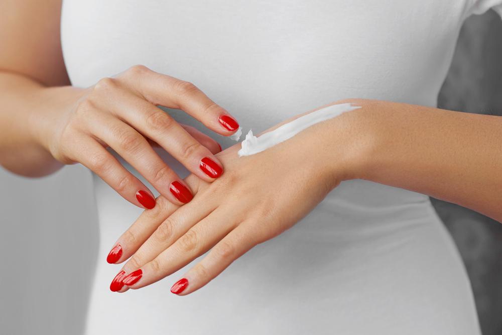 手の甲に日焼け止め効果のあるハンドクリームを塗っている女性