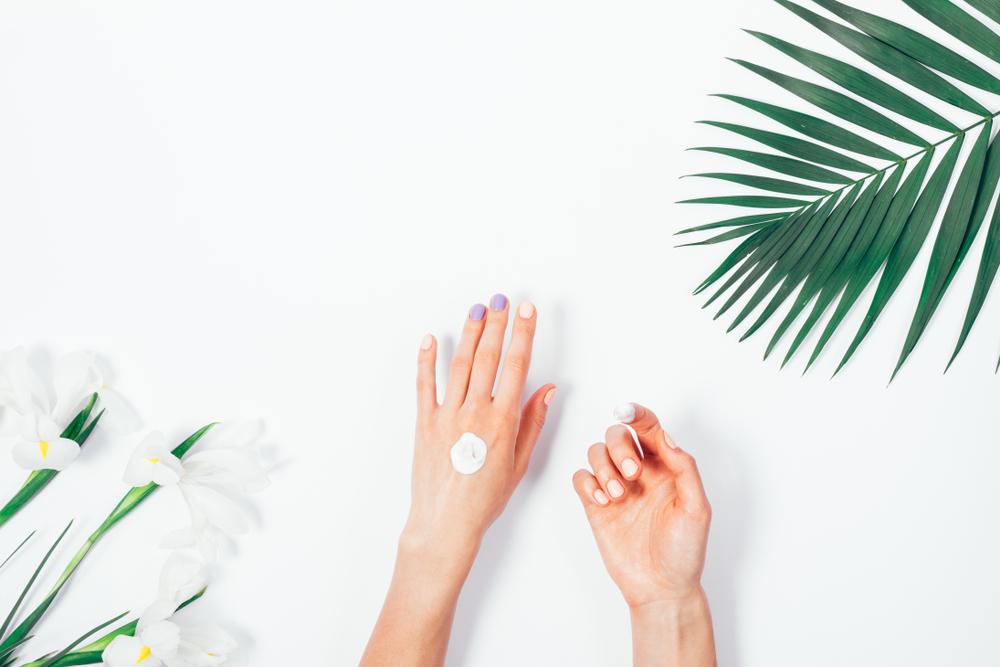 手の甲に日焼け止めクリームを塗っている女性