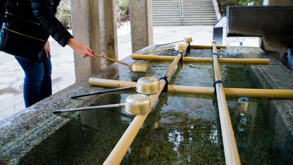 初詣に手水舎でお清めをしている女性