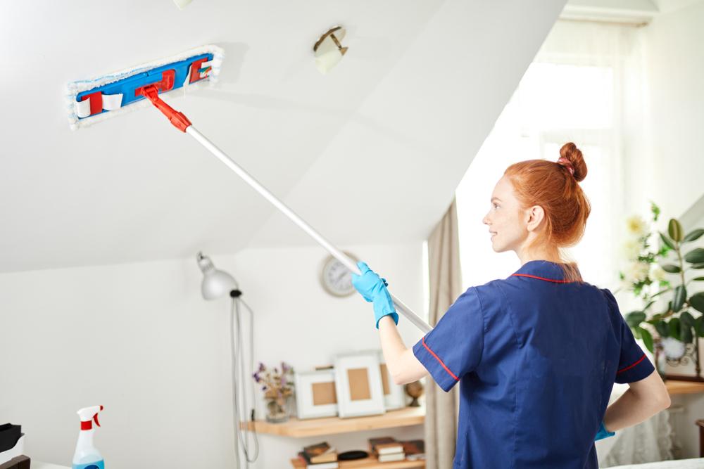 天井掃除をしている女性