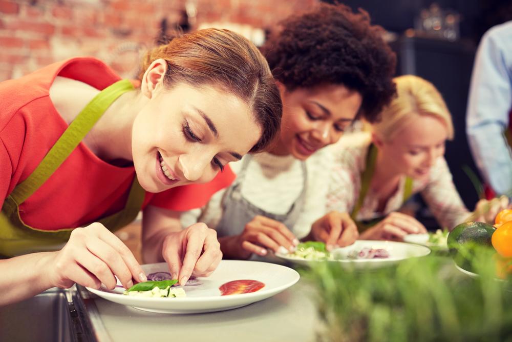 料理の盛り付けの基本を習っている女性達