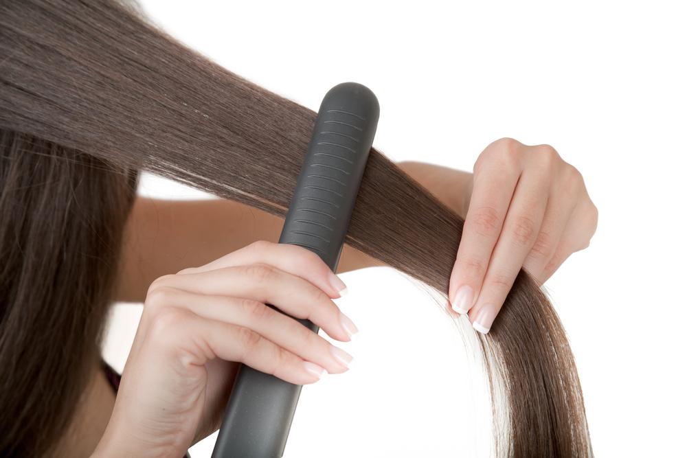 髪にヘアアイロンをかける女性