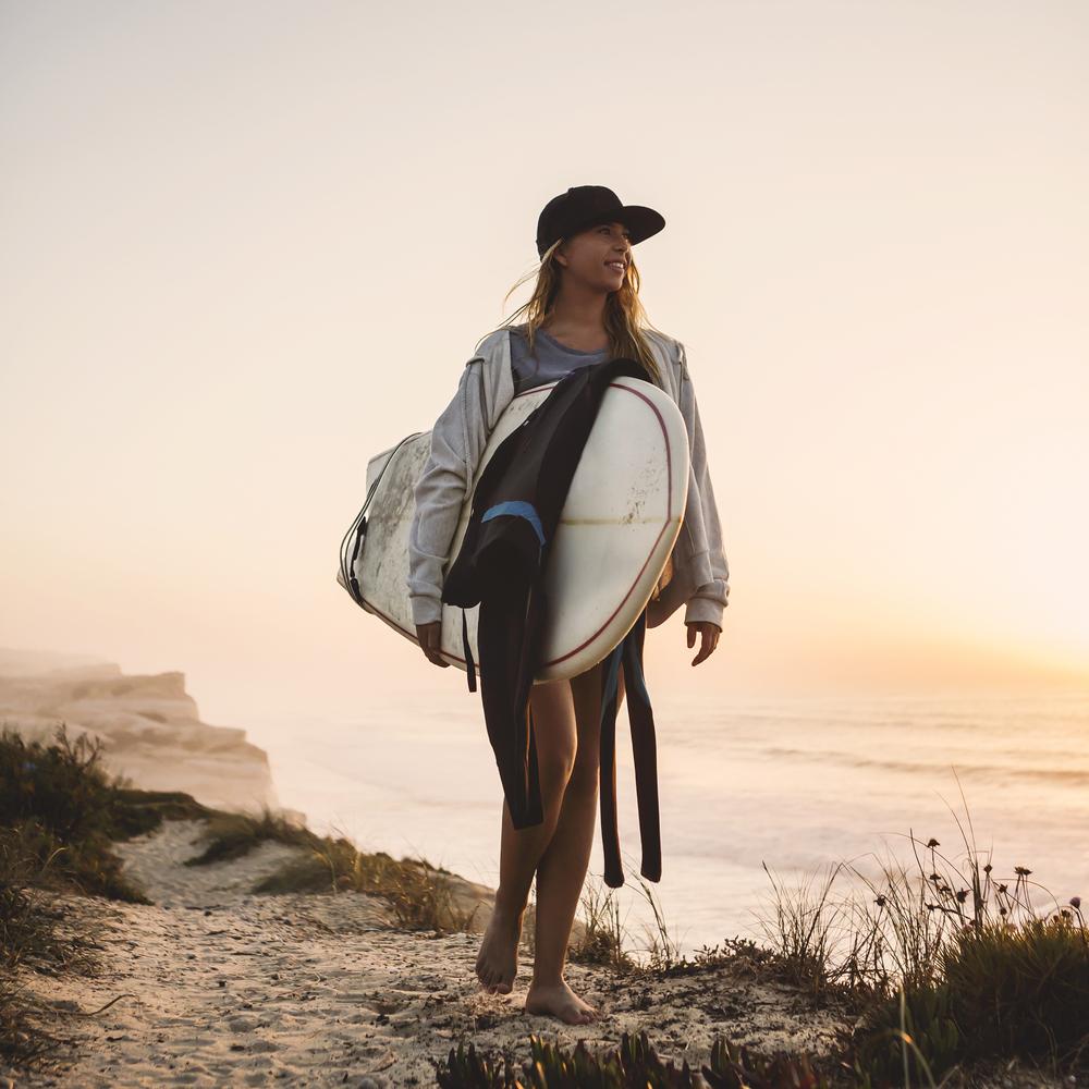 浜辺を歩くサーファーの女性