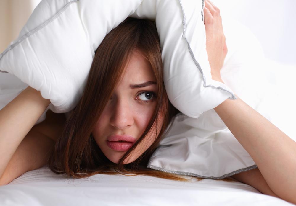 ベッドで頭を抱える女性
