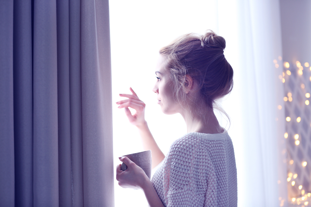 窓辺で温かいものを飲む女性