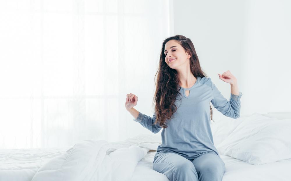ベッドから起き上がる女性