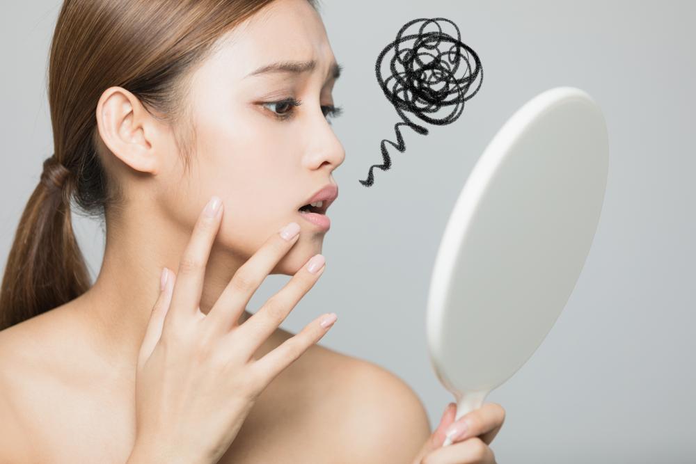 鏡を見て悩んでいる女性
