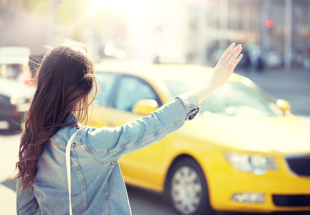 タクシーを呼ぶ女性