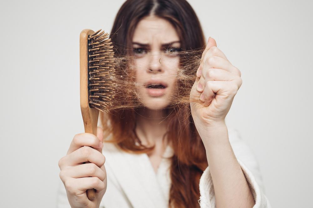 ブラシの髪の毛を取っている女性