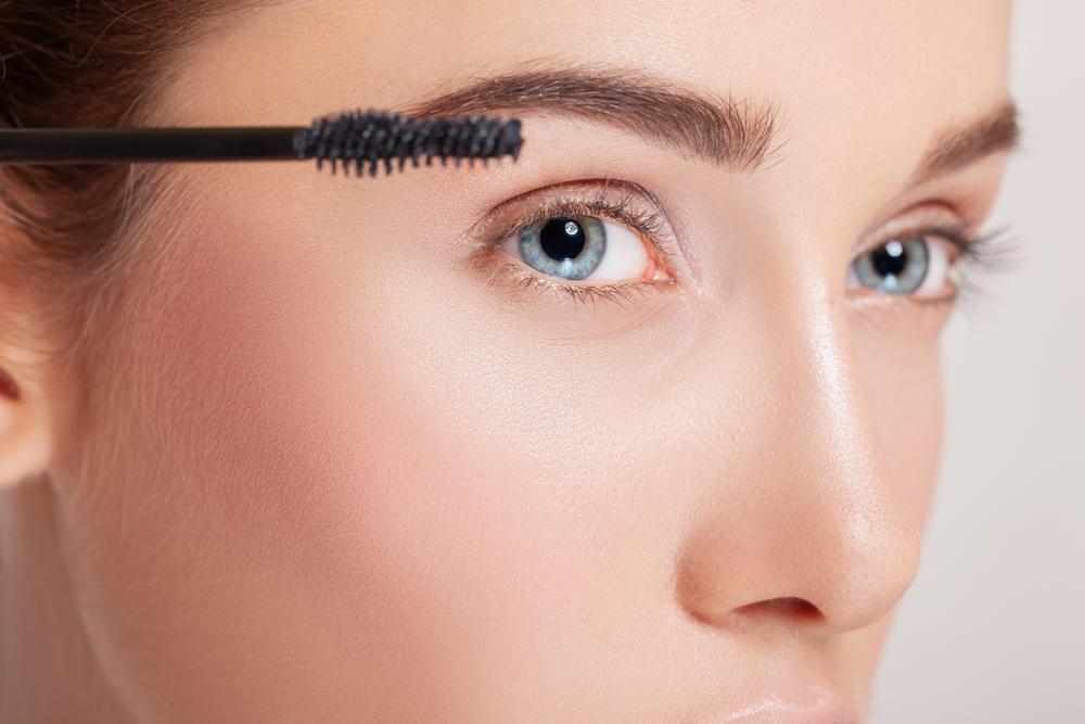 眉毛にマスカラを塗っている女性