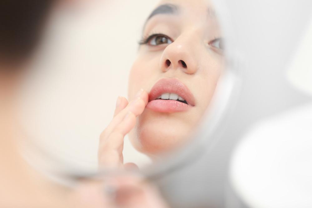 鏡で口元をチェックする女性