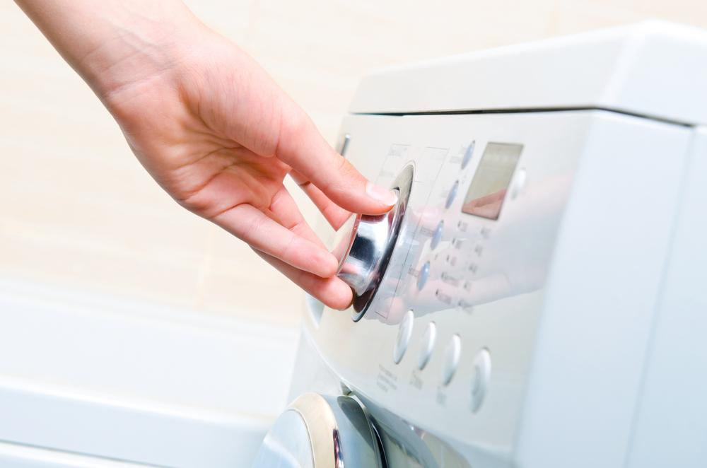 洗濯機で洗濯する女性の手元