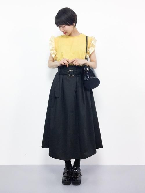 フリルトップスと黒のロングスカート