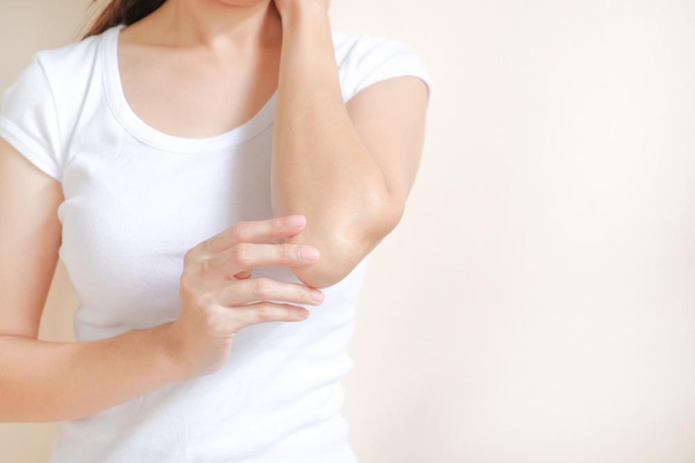 肘にボディクリームを塗る女性
