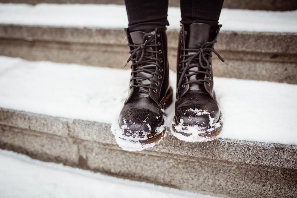 雪で革靴が濡れる女性の足元