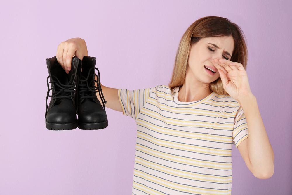 靴の臭さに顔をゆがめる女性