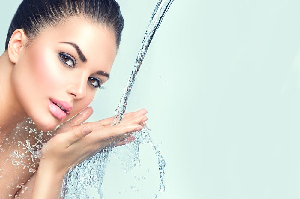 水を顔に当てている女性