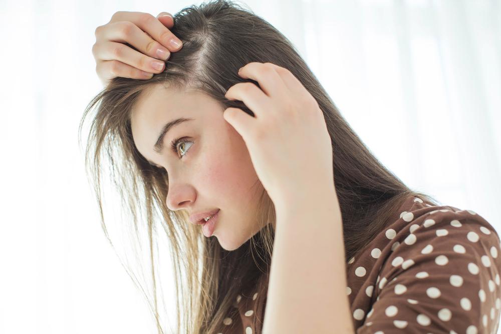 髪の毛の分け目が薄い女性