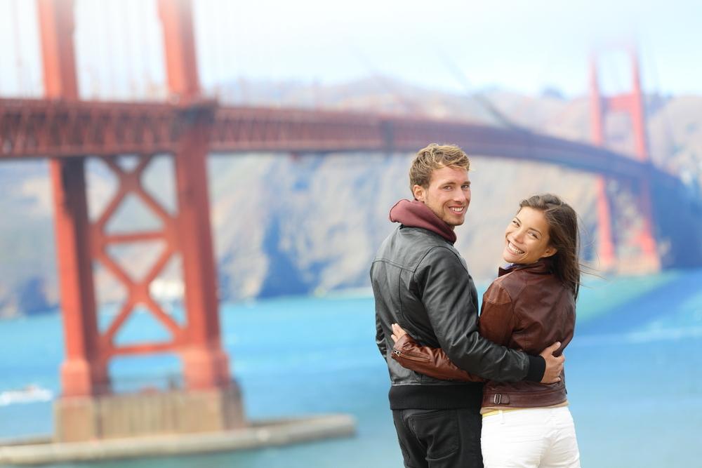 ゴールデンゲートブリッジの前で写真を撮るカップル