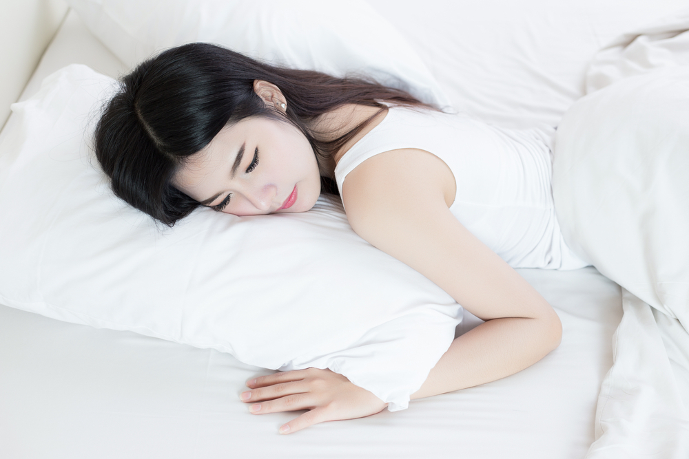 ロボット掃除機の稼働中に寝ている女性