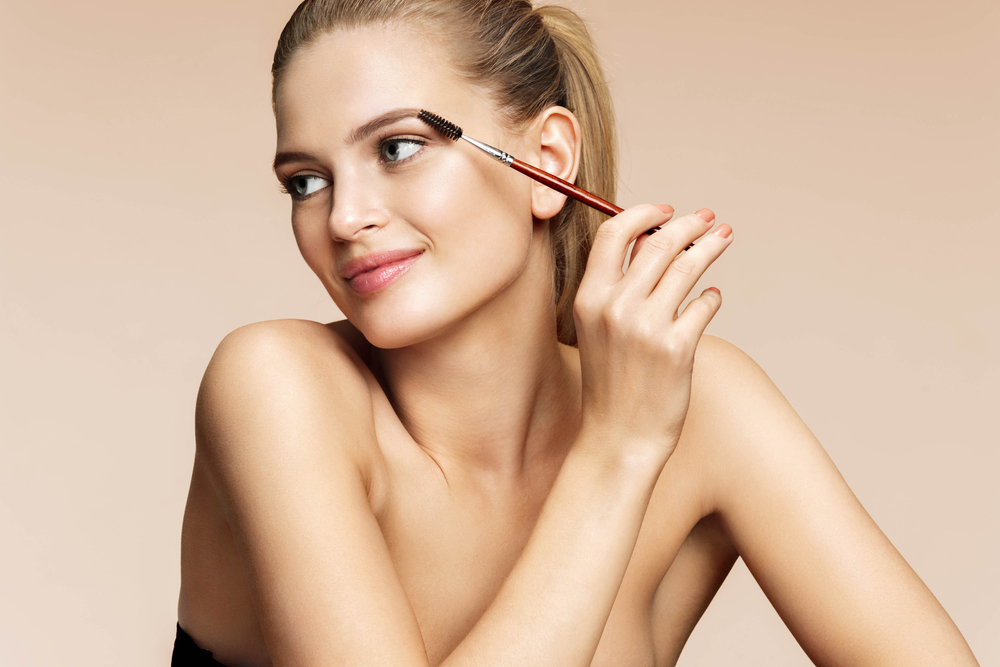 スクリューブラシで眉毛を整えている女性